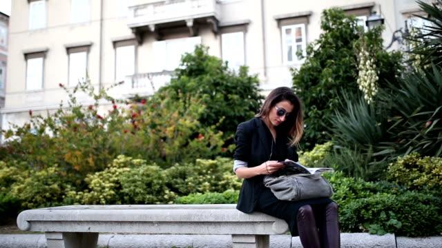 giovane donna leggendo una rivista seduto sulla panchina - panchina video stock e b–roll