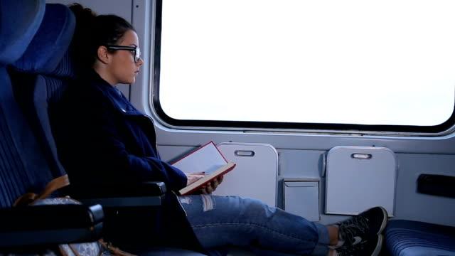 Jeune femme lisant sur un train