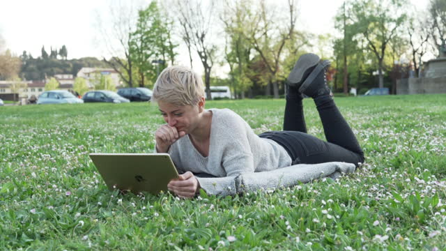 young woman reading on digital tablet at the park - one mid adult woman only stock videos & royalty-free footage
