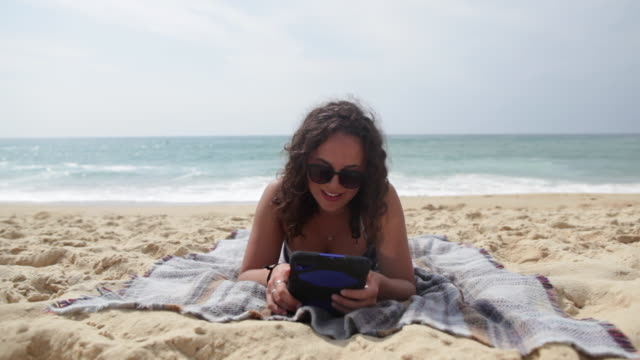 young woman reading on tablet laying at the beach in the south of france. - internet dating stock videos and b-roll footage
