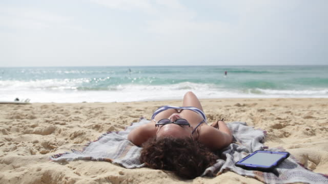 young woman reading on tablet laying at the beach in the south of france. - lying on back stock videos and b-roll footage
