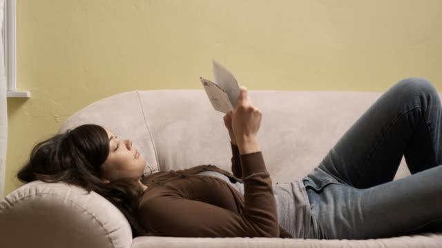 vídeos de stock e filmes b-roll de young woman reading the mail on a couch - correio