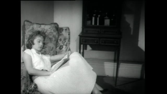 young woman reads in armchair by fireplace; 1958 - 1955 stock videos & royalty-free footage