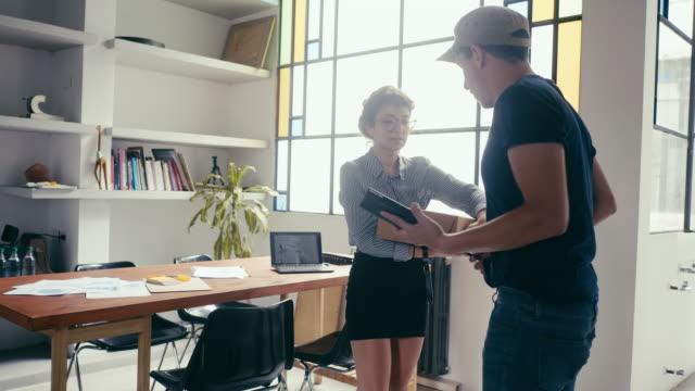 junge frau erhält ein paket im büro - unterschreiben stock-videos und b-roll-filmmaterial