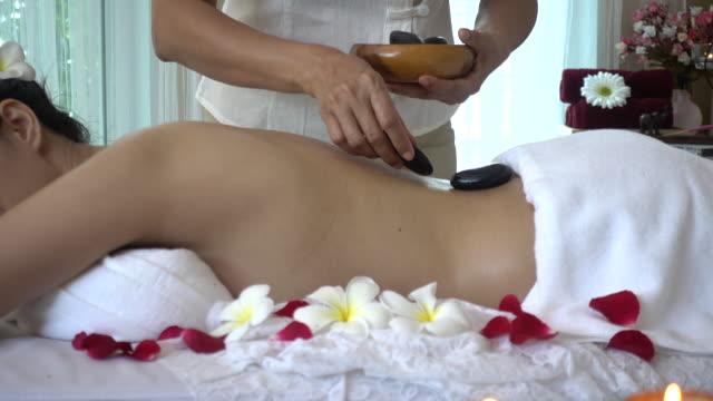 vídeos de stock, filmes e b-roll de jovem mulher recebendo massagem e quente spa pedra - health farm
