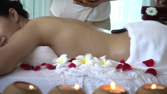 young woman receiving back massage and hot stone spa - construction material stock videos and b-roll footage