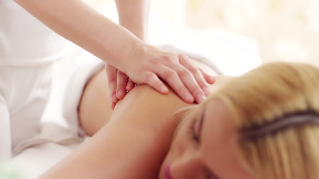 young woman receiving back massage - blonde hair stock videos & royalty-free footage