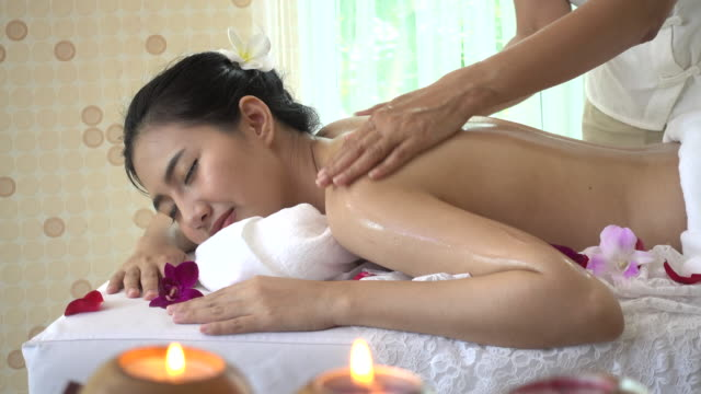 Young woman receiving back oil massage