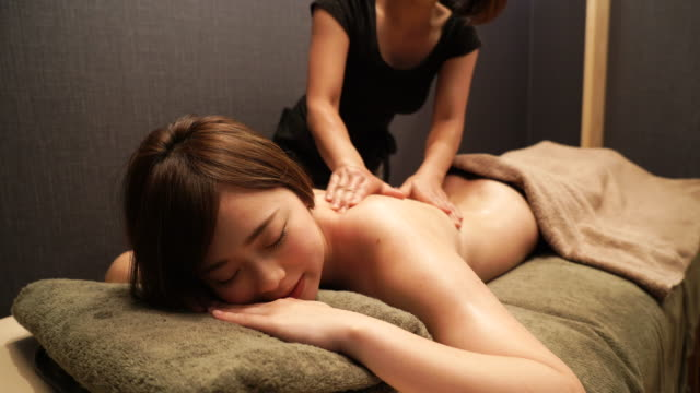 vídeos de stock e filmes b-roll de young woman receiving oil massage - spa treatment