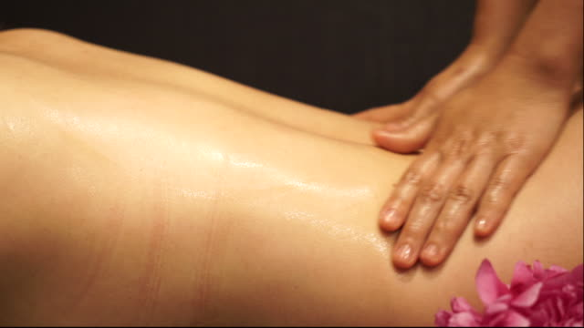 Young woman receiving oil massage