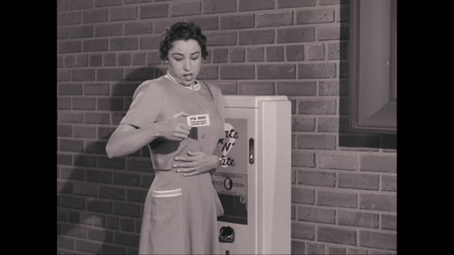 MS Young woman recieves fortune card from vending machine, showing surprise and then relief, then happiness / United States