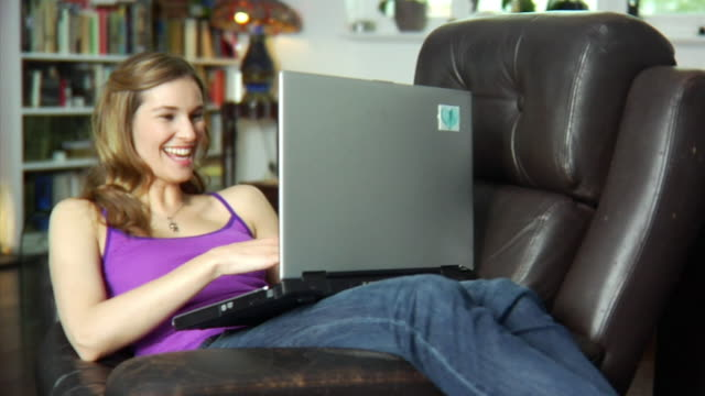 slo mo ms pan young woman reclining on sofa and using laptop / london, united kingdom - maglietta senza maniche video stock e b–roll