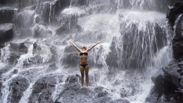 Junge Frau erfrischend an einem Wasserfall mit ihren ausgestreckten Armen
