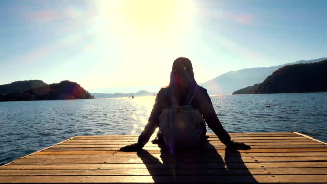 Young woman relax sitting on pier at the lake