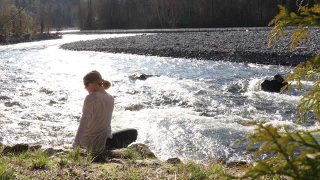 junge frau entspannt am flussrand, führt yoga-moves durch - part of a series stock-videos und b-roll-filmmaterial