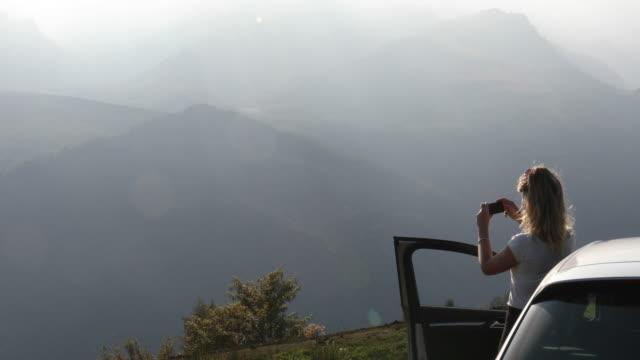 vídeos de stock e filmes b-roll de young woman relaxes by car door in mountains - temas fotográficos