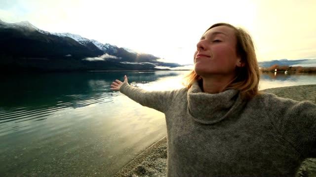 Jeune femme se détend au bord du lac en automne