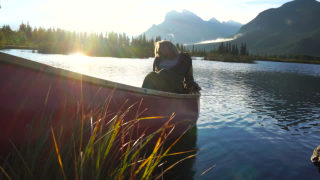 Young woman relaxes in canoe, on mountain lake