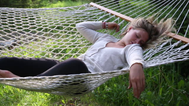 young woman relaxes in hammock, in forest meadow setting - collant video stock e b–roll