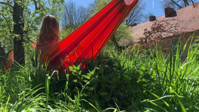 young woman relaxes in hammock on a beautiful summer day - formal garden stock videos & royalty-free footage