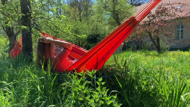 young woman relaxes in hammock on a beautiful summer day - woman hands behind head stock videos & royalty-free footage