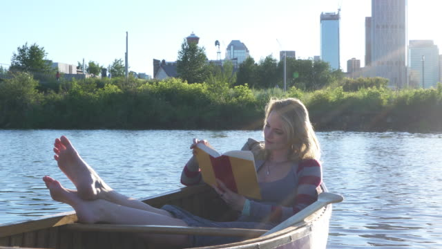 Young woman relaxes in wooden canoe, reading book, city pond