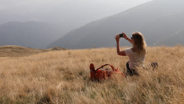 vídeos de stock e filmes b-roll de young woman relaxes on grassy mountain slope, taking pic - temas fotográficos