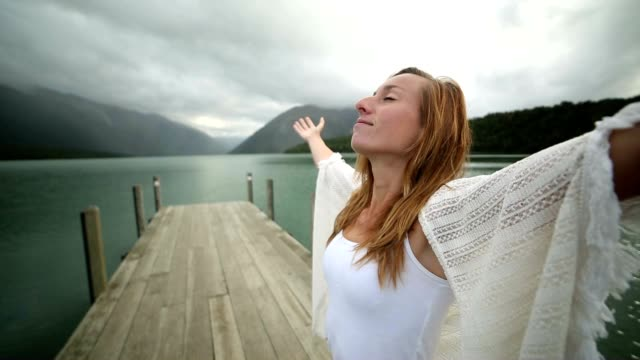 young woman relaxes on lake pier, stands arms outstretched - māori people stock videos & royalty-free footage