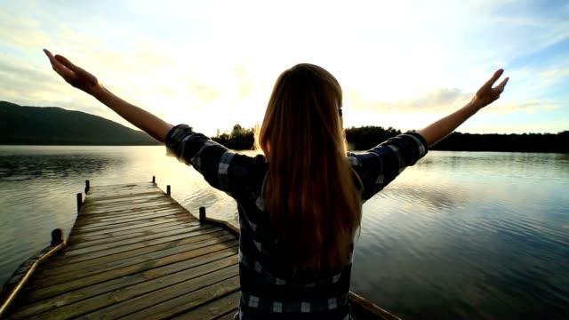 stockvideo's en b-roll-footage met jonge vrouw ontspant op lake pier, stands van uitgestrekte armen - steiger pier