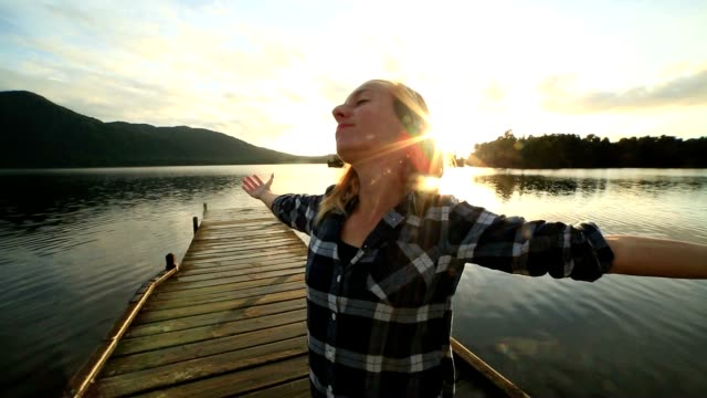 young woman relaxes on lake pier, stands arms outstretched - jetty stock videos & royalty-free footage