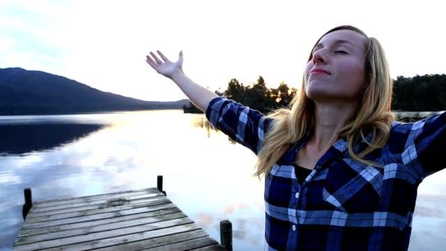 Junge Frau entspannt auf See Pier, steht Ausgestreckte Arme