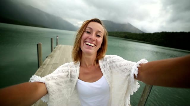 Young woman relaxes on lake pier, takes a selfie portrait