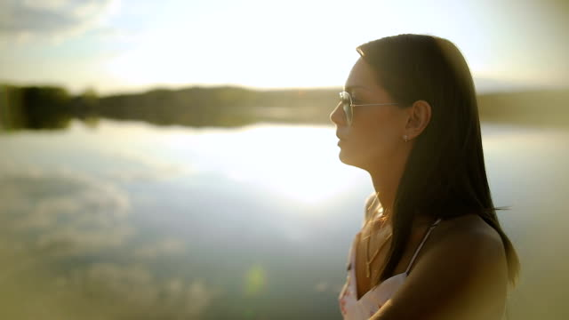 vídeos de stock e filmes b-roll de young woman relaxes on lake pier, watches sunset through her sunglasses.beautiful autumn day - óculos de sol