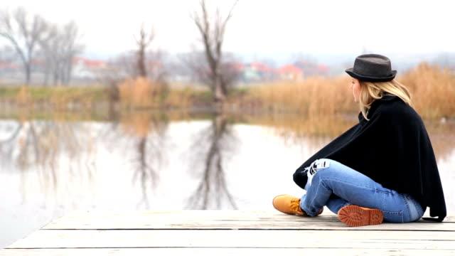 Junge Frau entspannt auf See mit Decke