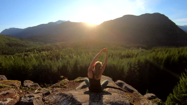 young woman relaxes on mountain ledge, contemplative - cross legged stock videos & royalty-free footage