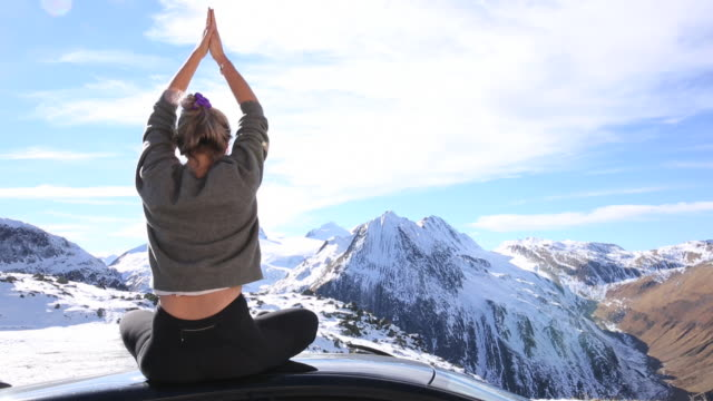 young woman relaxes on roof of car, mountain pass - person sitting cross legged stock videos & royalty-free footage