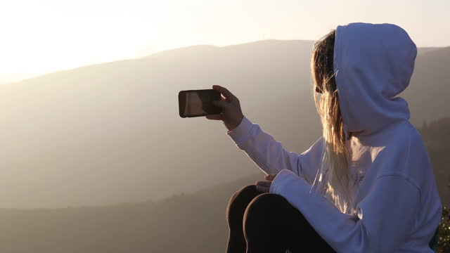 young woman relaxes on summit of mountain overlook, enjoys view - photo messaging点の映像素材/bロール