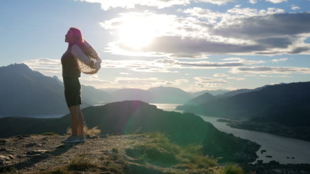 young woman relaxing after summit on the top of mountain , queenstown , otago , new zealand - on top of stock videos & royalty-free footage