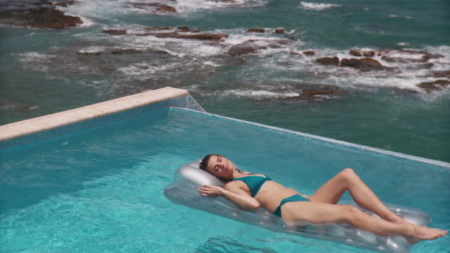 ws young woman relaxing and floating on inflatable raft in infinity pool with ocean in background/ scarborough, tobago, trinidad and tobago - inflatable raft stock videos and b-roll footage