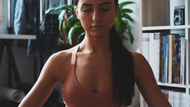 young woman relaxing and practicin breathing exercise at home - mudra stock videos & royalty-free footage