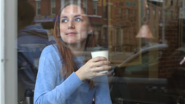 A young woman relaxing at a cafe, having a cup of coffee