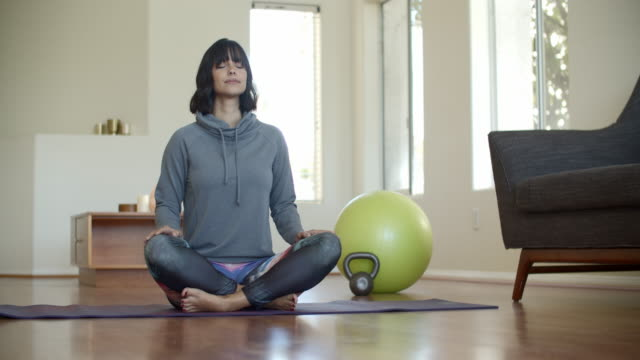 young woman relaxing at home doing yoga - cross legged stock videos & royalty-free footage