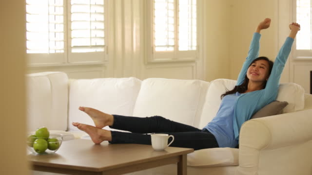 ms young woman relaxing at home. - sofa stock videos & royalty-free footage