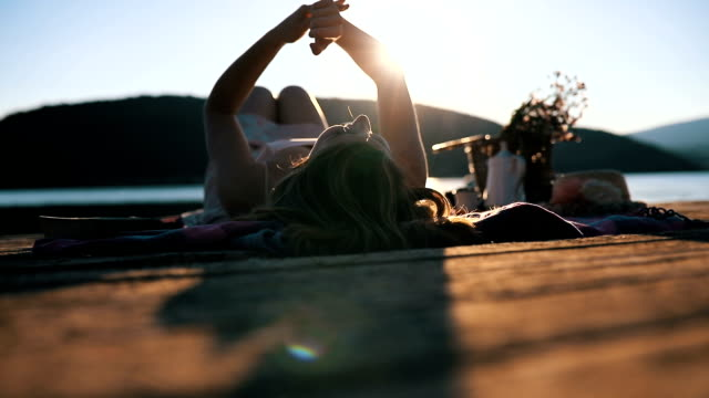 stockvideo's en b-roll-footage met jonge vrouw ontspannen aan het meer - steiger pier
