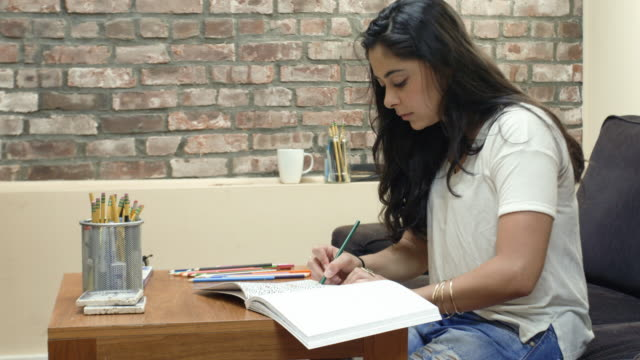 young woman relaxing by coloring in an adult coloring book - interior - 4k - summer - lebanese ethnicity stock videos and b-roll footage