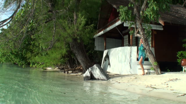 Young woman relaxing by her bungalow walking on cean shore