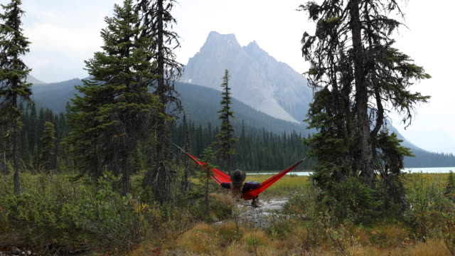 A young woman relaxing in a hammock by a lake surrounded by mountains.