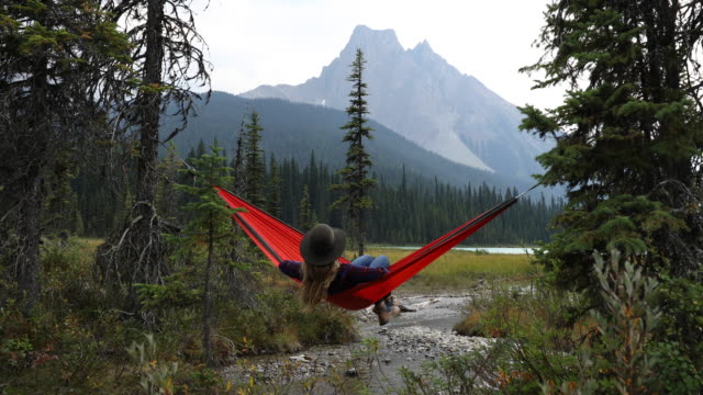 vídeos de stock, filmes e b-roll de a young woman relaxing in a hammock by a lake surrounded by mountains. - alberta