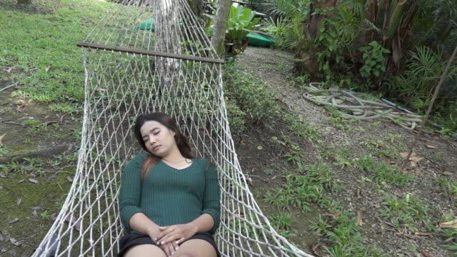 リラックスできる若い女性のスーパースローモーションのハンモック - ハンモック点の映像素材/bロール