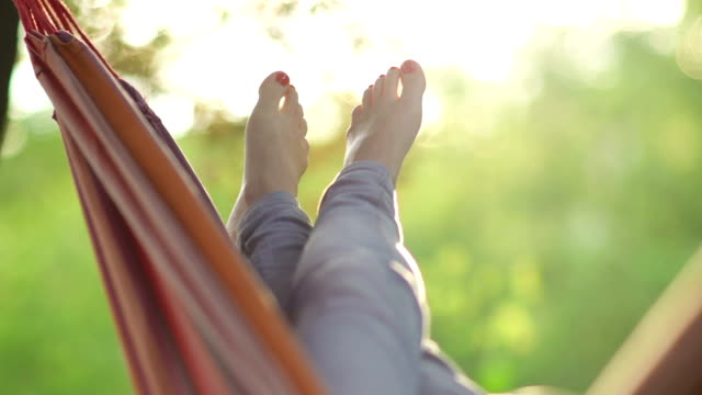 young woman relaxing in a hammock under the trees - hammock stock videos & royalty-free footage